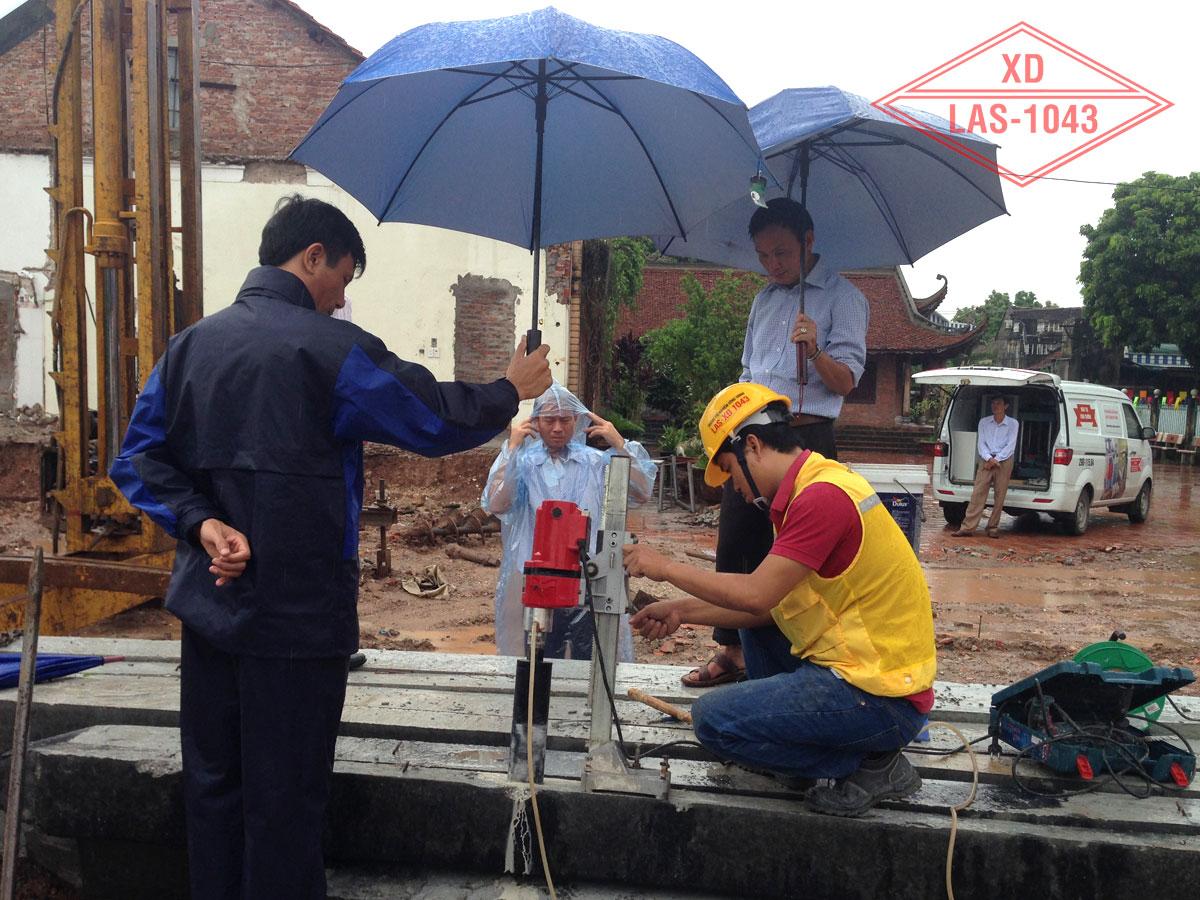 Đích thân Chánh xứ giám sát khoan lấy mẫu và cầm ô che mưa cho thí nghiệm viên